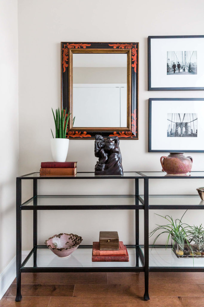Glass console table with red accents, black and white Brooklyn photographs