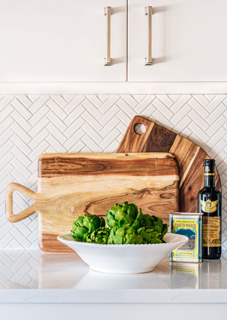 Cutting board vignette on quartz with white herringbone tile and avocados