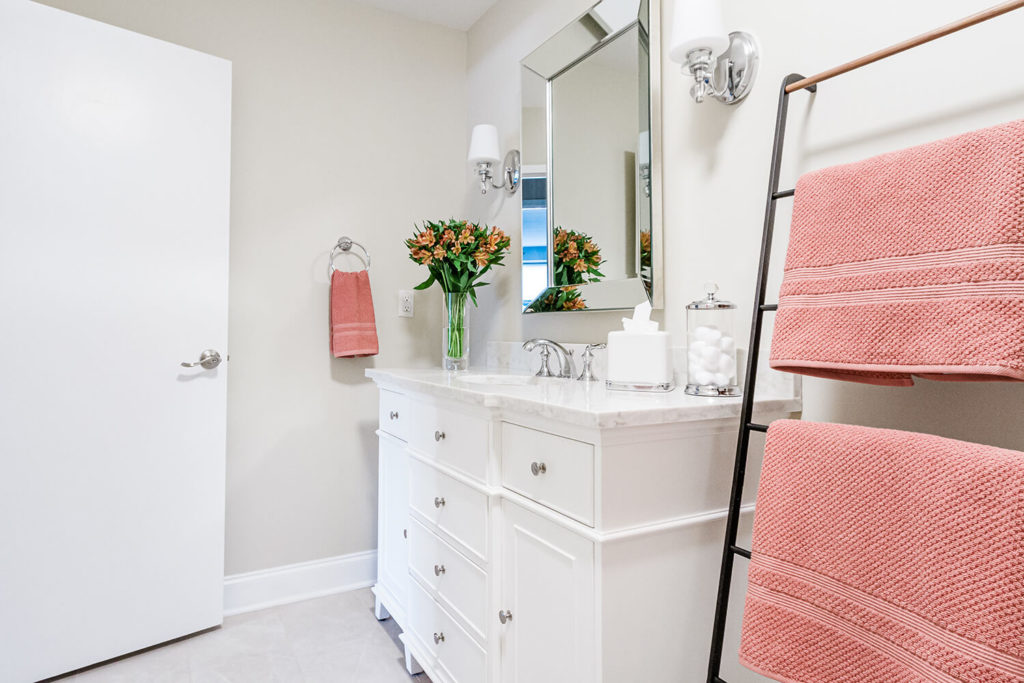 Guest bathroom renovation in white and greige with salmon pink accents