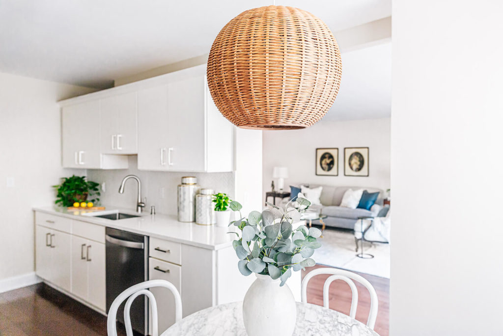 Wicker rattan pendant over marble bistro table in updated white galley kitchen