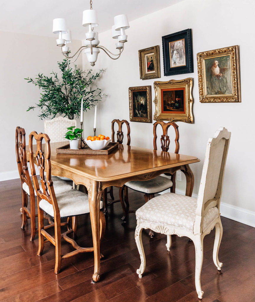 French inspired taupe formal dining room, gold frame antique art gallery, olive tree, slipper foot dining table and curvy, feminine chairs